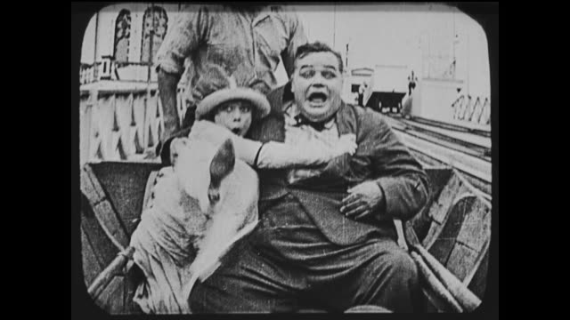 vidéos et rushes de 1917 man (fatty arbuckle) has scary time on water ride with date, falls off ride and into water - attraction foraine équipement de loisirs