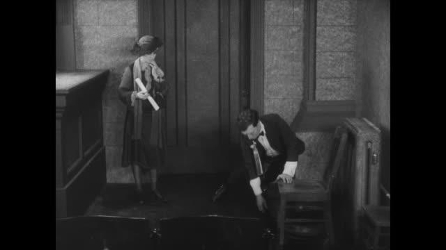 vídeos y material grabado en eventos de stock de 1927 man (buster keaton) has trouble bending over in his ill fitted suit - changing form