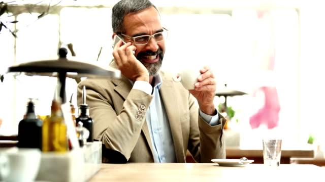 Mann mit einem Kaffee und reden über ein Handy.