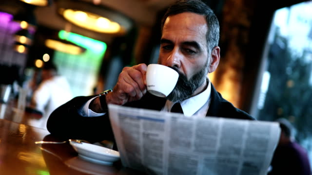 man having a morning coffee in a bar - barba peluria del viso video stock e b–roll