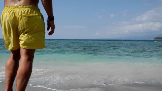 man har en simtur i gili travangan beach på bali - människoarm bildbanksvideor och videomaterial från bakom kulisserna