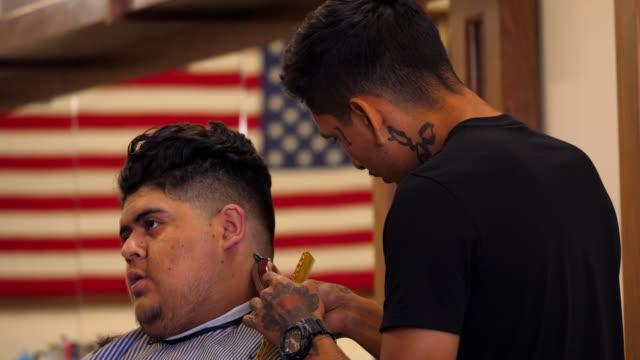 MS Man having back of neck trimmed during hair cut in barber shop