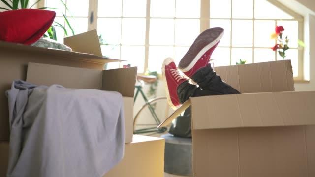 彼の新しい家でダンボール箱に楽しんでいる男 - 段ボール箱点の映像素材/bロール