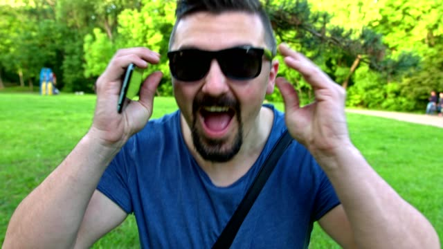Man having fun laughing and putting on his sunglasses while looking at the camera