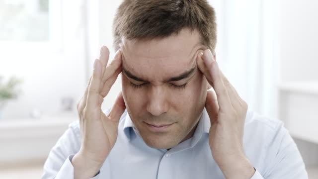 vídeos y material grabado en eventos de stock de hombre con dolor de cabeza  - dolor de cabeza