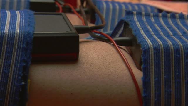 vidéos et rushes de zo, cu, man having infrared muscle stimulation treatment, close-up of leg - spa treatment
