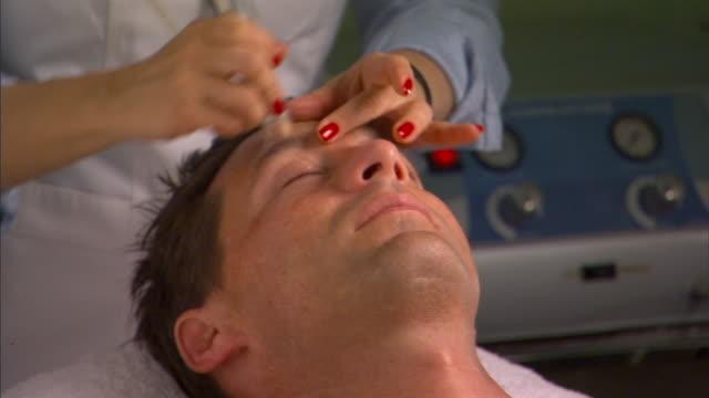 cu, man having microdermabrasion treatment - schönheitssalon stock-videos und b-roll-filmmaterial