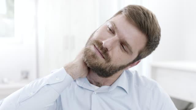 vídeos de stock e filmes b-roll de man having neck pain - dor no pescoço