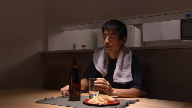 MS, Man having snack and beer at kitchen table at night