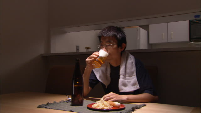 ms, man having snack and beer at kitchen table at night - beer bottle stock videos & royalty-free footage