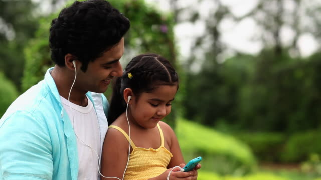 Man hearing music with his daughter on a mobile phone