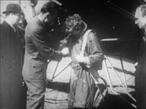 B/W 1930 man helping Amelia Earhart put on flight suit / Pennsylvania / newsreel