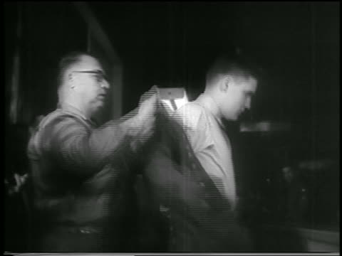 b/w 1958 man helping elvis presley put on army jacket / fort chaffee arkansas / newsreel - early rock & roll stock videos and b-roll footage