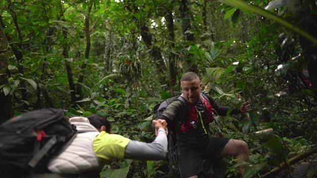 vídeos de stock, filmes e b-roll de homem ajudando amigo durante caminhada em uma floresta - ecoturismo