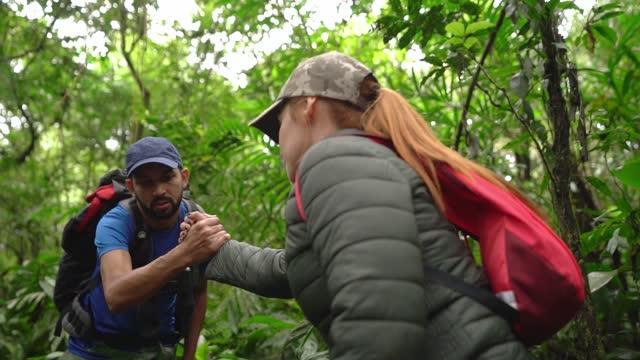 stockvideo's en b-roll-footage met mens die vriend helpt tijdens het wandelen in een bos - begeleiding