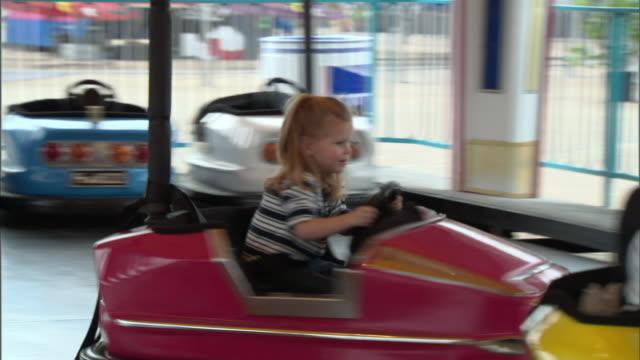 ms, pan, man helping girl (2-3) spinning in bumper car, dallas, texas, usa - bumper car stock videos & royalty-free footage
