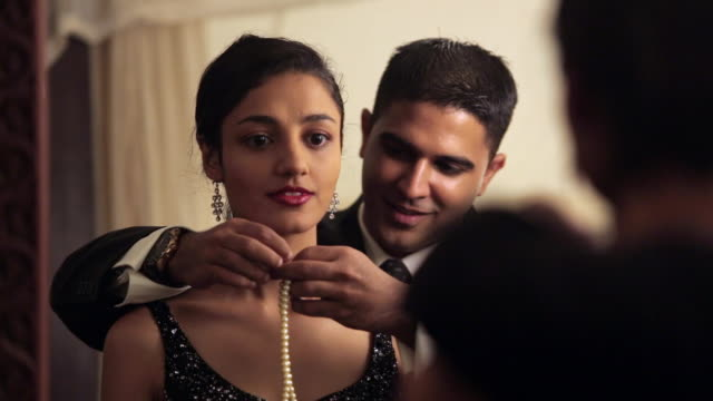 ms selective focus man helping girlfriend with pearl necklace / singapore - orecchini video stock e b–roll