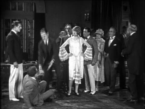 b/w 1926 man (charley chase) helping man up from floor as group exits room / feature - 1926 stock videos & royalty-free footage