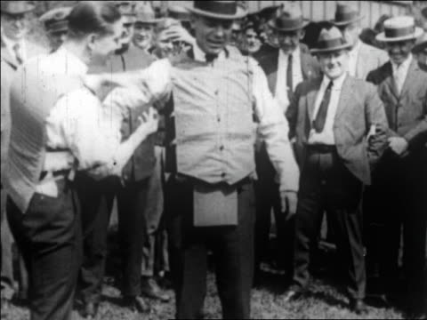 vídeos de stock, filmes e b-roll de b/w 1922 man helping second man put on bullet-proof vest / newsreel - vest