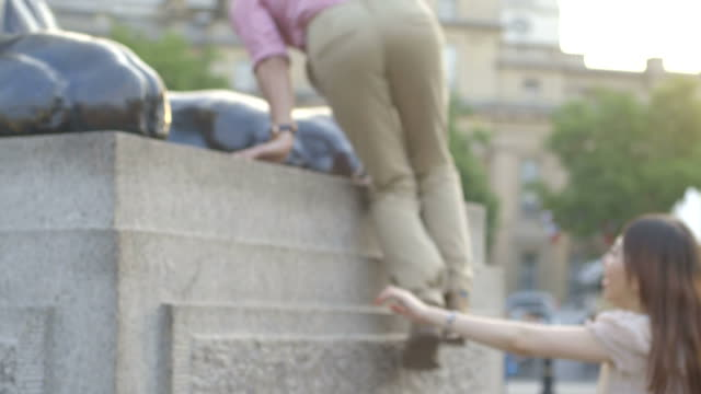 Man helping woman to climb on pedestal on trafalgar square