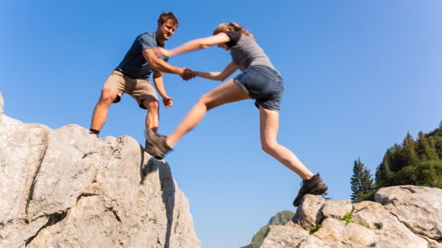 Man helping women to jump gap in mountain boulder