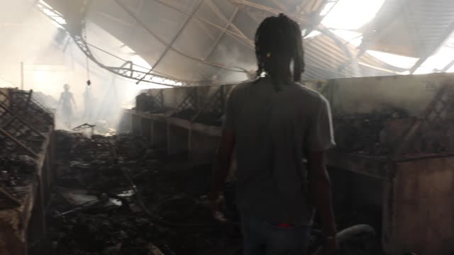 A man helps firefighters work to put out a blaze at PortauPrince's historic Iron Market on February 13 2018 in PortauPrince Haiti Hundreds of locals...