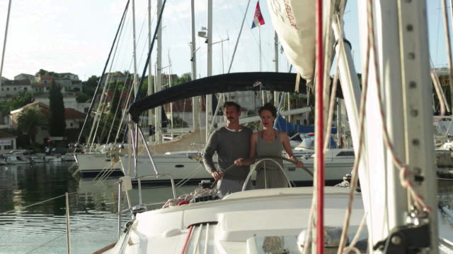 Man helps woman to steer yacht out of marina.
