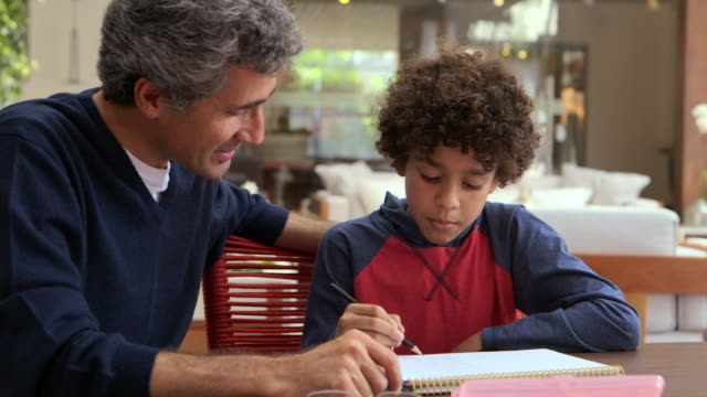 vídeos de stock, filmes e b-roll de medium handheld man helps young boy study and read sitting at table and they look at each other - família de duas gerações