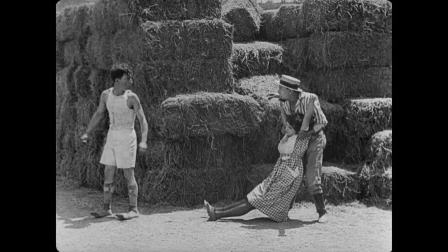 1920 Man (Buster Keaton) hides as scarecrow to escape pursuer
