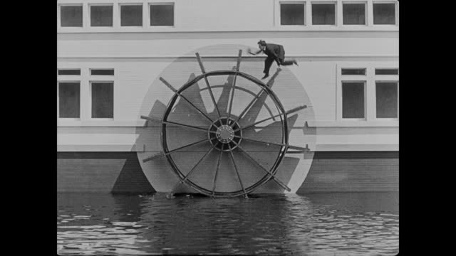 1922 man (buster keaton) hides from the cops on a boat's paddle wheel and is forced to run in it like a hamster wheel once the boat starts - paddle boat stock videos & royalty-free footage