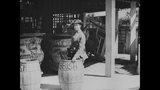 1917 Man (Buster Keaton) hides in garbage barrel to gain free entrance into Coney Island