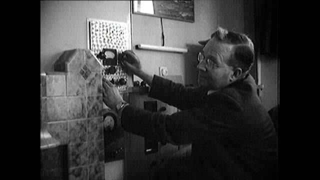 b&w man hides television in living room; uk, 1948 - painting stock videos & royalty-free footage