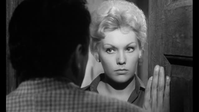 1955 man (frank sinatra) hides while one of woman's (kim novak) suitor comes knocking - 懇願する点の映像素材/bロール