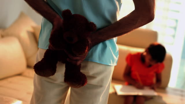 Man hiding a teddy bear from his daughter