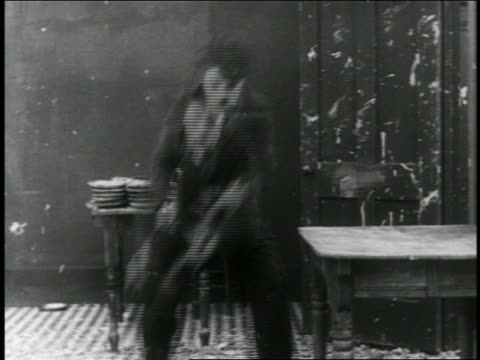 b/w 1916 man hiding behind table in pie fight / short - 1916 stock videos & royalty-free footage