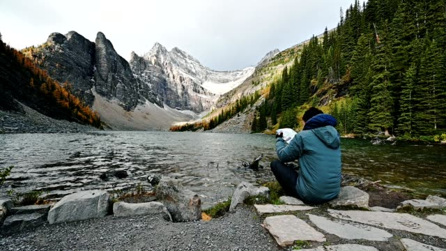 man hiker are sitting to see the map for travel in anges lake - banff national park stock videos & royalty-free footage