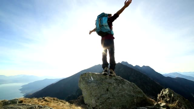 man hiker arms outstretched on mountain ridge crest - rucksack stock videos and b-roll footage