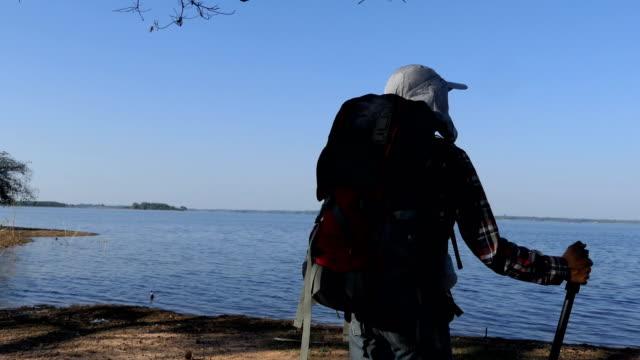 vídeos y material grabado en eventos de stock de excursionista de hombre con mochila cerca del lago - espalda humana