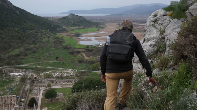 man hikes above ruins of ancient greek civilization - old ruin stock videos and b-roll footage