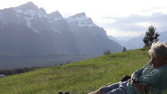 vídeos de stock, filmes e b-roll de homem caminha pelo prado da montanha, relaxa em gramíneas - smart