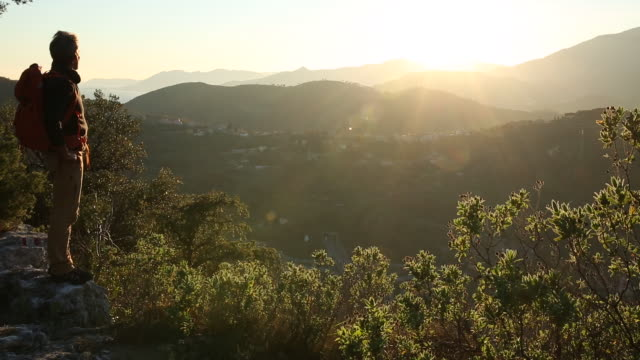 Man hikes to cliff edge, looks out to hills and sunrise