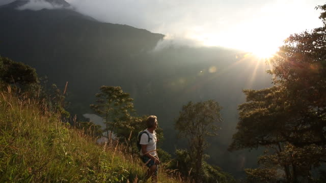 Man hikes up mountain slope, sunrise over ridge behind