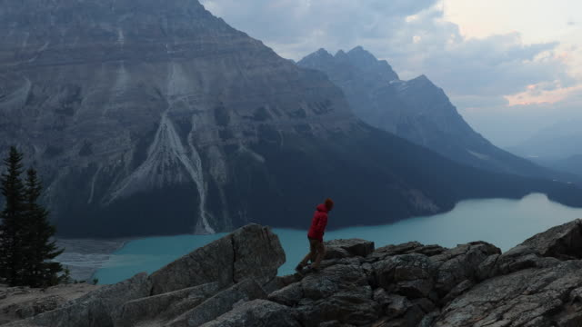 a man hiking a rocky trail high above a lake. - kanada stock-videos und b-roll-filmmaterial