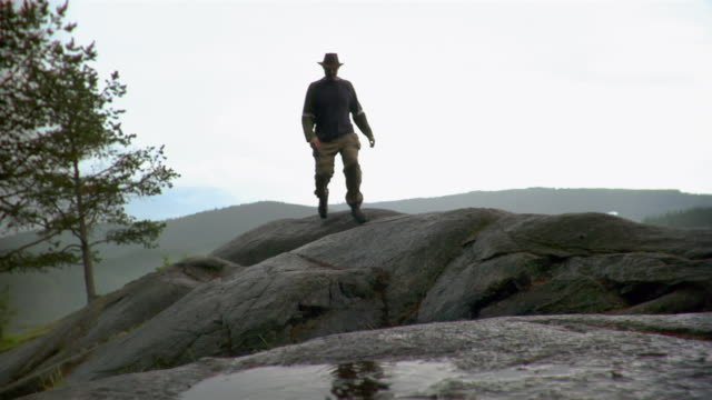 man hiking across bluff / ground level view of man stepping through puddle - kelly mason videos stock-videos und b-roll-filmmaterial