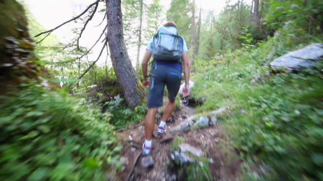 A man hiking and backpacking on a trail in the mountains.