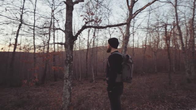 Man wandelen en verkennen van bosgebied bij zonsondergang