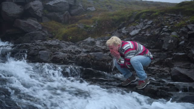 vídeos y material grabado en eventos de stock de a man hiking near a stream river and drinking the water in iceland, europe. - slow motion - riachuelo