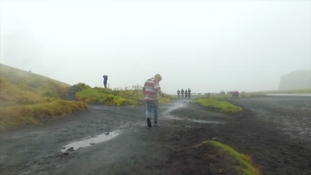 A man hiking near a waterfall in Iceland, Europe. - Slow Motion