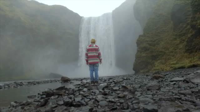 A man hiking near Skogafoss waterfall in Iceland, Europe. - Slow Motion