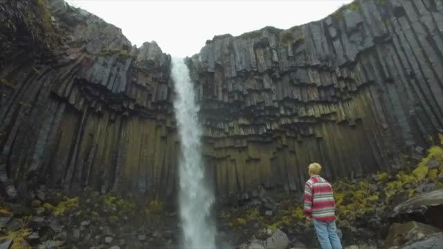 A man hiking near Svartifoss Waterfall in Skaftafell in Vatnajokull National Park river flowing in Iceland, Europe. - Slow Motion